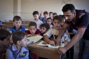 Un insegnante con gli alunni in una scuola di Aleppo (Ansa)